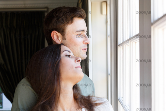 Caucasian couple looking out of window smiling woman leaning on man