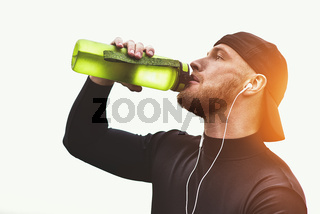 Muscular bearded athlete drink a water after good workout session on city park.