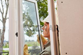 Fenstermonteur baut Fenster ein auf Baustelle