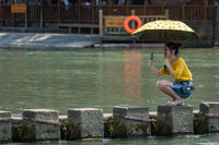 Chinese woman taking selfie on stepping stones in Fenghuang