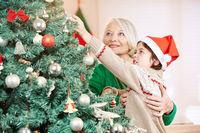 Großmutter und Enkel schmücken Weihnachtsbaum