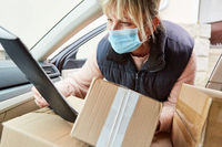 Paketbotin mit Mundschutz prüft Lieferung im Innenraum