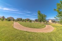 Pathway curving through vast grassy field with homes lake and mountain view