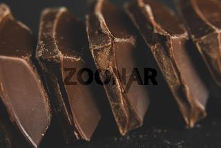 Broken dark chocolate blocks stack on black background