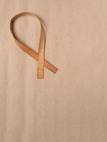Wooden edge veneer curl on a natural paper,symbol for Liver Cancer awareness, World Cancer Day