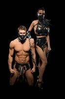 Man and dominate woman in BDSM outfit looking at camera