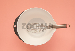 Whisk and a plastic cup for whipping on a pink background.