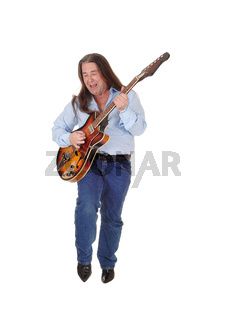 Man singing and playing the guitar in the studio full body