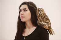 Woman in witch costume holding owl