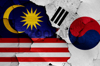 flags of Malaysia and South Korea painted on cracked wall