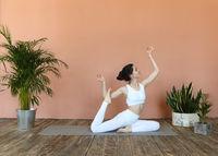 Slim woman doing yoga on terracotta background