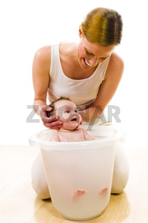 Mom bathing cute baby girl