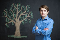 Photo of young businessman on chalkboard background. Dollar tree painted on chalkboard