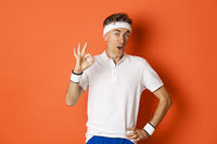 Concept of sport, fitness and lifestyle. Portrait of amazed adult man in workout uniform, showing okay sign and looking impressed, standing over orange background