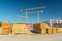 Piles of wood in front of large construction site with cranes