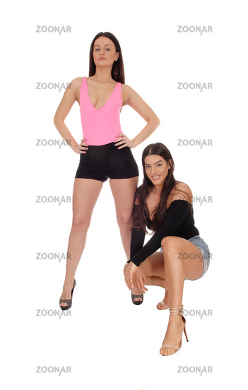 Two beautiful women standing and kneeling in shorts in the studio