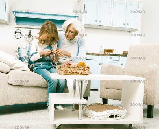Grandmother helps her granddaughter while she learning how to knit