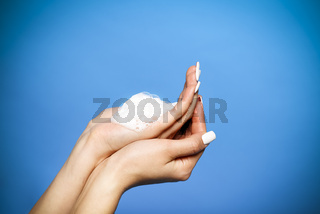 Young caucasian woman washing her hands with foam