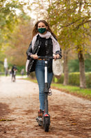 Casual caucasian teenager wearing protective face mask riding urban electric scooter in city park during covid pandemic. Urban mobility concept