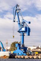 Blue crane unload cargo in a seaport in Sweden