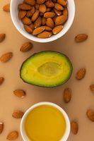 Avocado and bowls of almonds and dressing on orange background