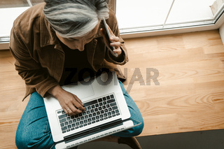 Grey haired woman speaking on mobile phone while working with laptop computer. Talking mature woman sitting on wide wooden window sill. Top view. Tinted image
