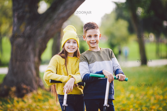 Twins 10 years old in bright clothes spend time actively together in autumn park riding kick scooters. Happy children. Eco transport. Kids posing in fall park. Brother and sister pre teens portrait