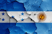 flags of Honduras and Argentina painted on cracked wall