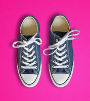 Blue sneakers isolated on pink background