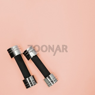 Metal small dumbbells on a pink background.