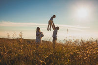 The concept of family and love. Parents with their son in summer field