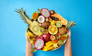 hands holding plate of exotic fruits over blue