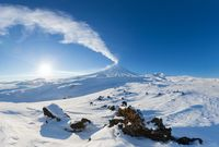Kamchatka Peninsula, winter mountain landscape, beautiful panoramic view of eruption active volcano in clear sunny weather with blue sky