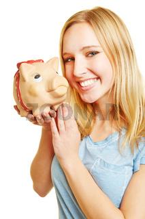 Junge Frau lacht mit Sparschwein