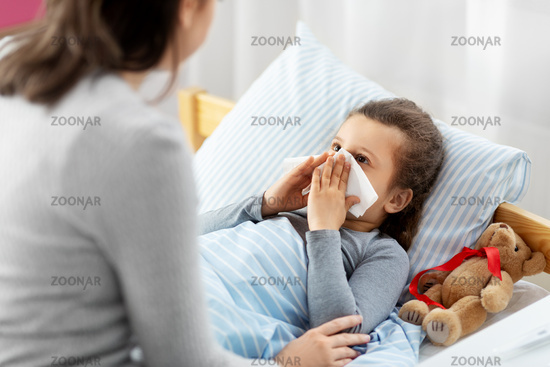 mother and ill little daughter blowing nose in bed