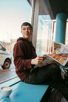 Portrait of man sitting at a cafe, reading newspapers and drinking coffee