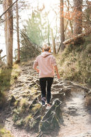 Rear view of active sporty woman listening to the music while running in autumn fall forest. Female runner training outdoor. Healthy lifestyle image of young caucasian woman jogging outside