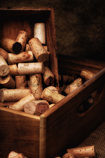 Wooden boxes full of  used wine corks with strong warm side light. Vertical format with copy space with a dark brown mottled background.