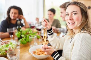 Freunde essen gemeinsam Spaghetti mit Tomatensauce in WG