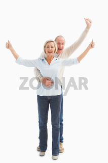 Happy mature couple cheering at camera