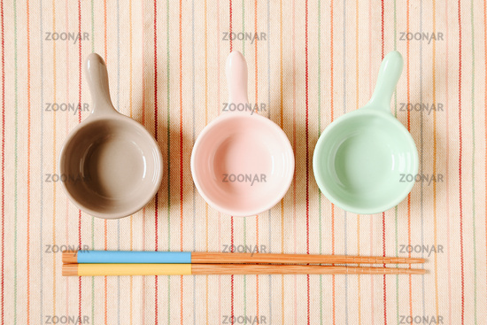 Plate and chopsticks on fabric background