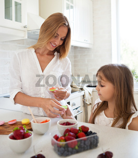 Woman cooking macarons at the kitchen with her little daughter