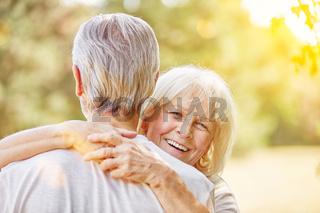 Lachende alte Frau umarmt Mann