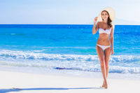 Girl in bikini and sunhat on beach