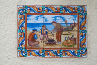 BARCELONA, SPAIN - JUNE 2, 2013: Picture of a mosaic depicting the fisher in Spain. An image of specially painted tiles and pieces of glaze on the wall of a house in Barcelona
