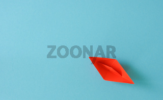 Orange paper ship on blue background with space for text