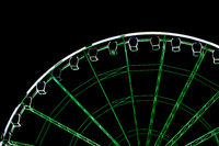 detail view of an illuminated green and white ferris wheel and cabins in black night
