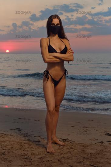 Sensual pretty girl wear black color cloth mask and bikini pose on nature at sunrise near sea. Concept covid-19 outbreak. Obligatory compulsory use face masks outdoors. Fashion and beauty full length