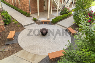 Aerial view of benches and fire pit on circular paved patio outside a building