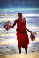 Commercial portrait of young tribal Masai warrior man on hot bright sunny African beach